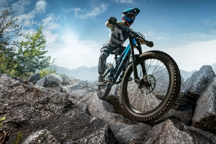 MTB rider with mountain bike on stony terrain