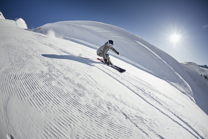Skier with optical ski goggles on a fast downhill slope on the ski slope