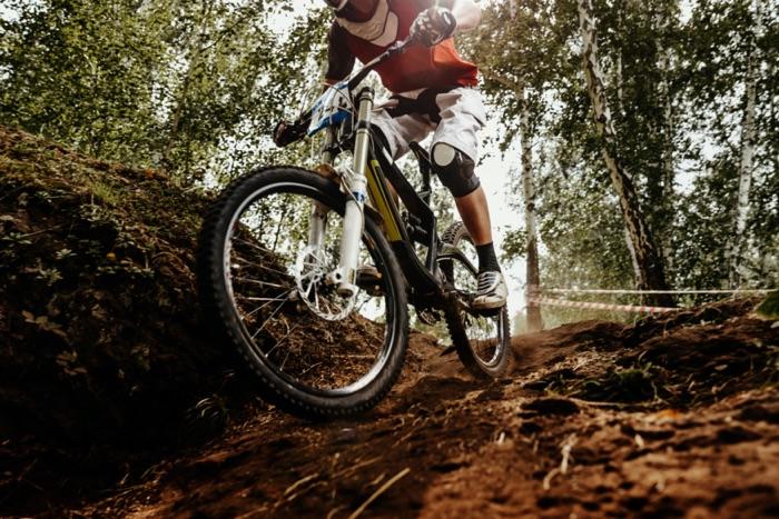 Ciclisti in mountain-bike che guidano in discesa nella foresta con gli occhiali di protezione ottici