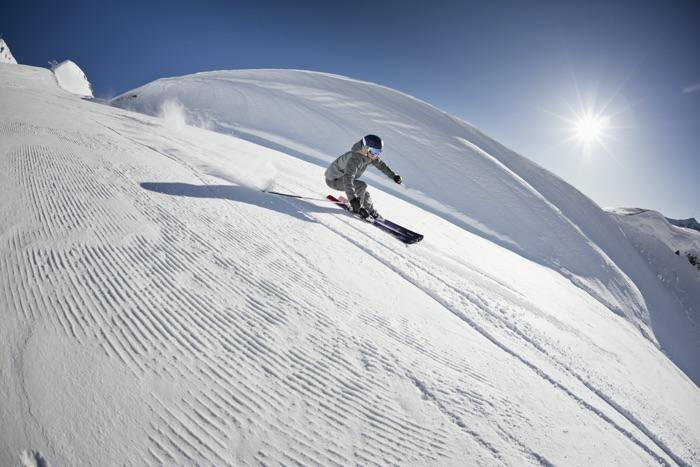 Skifahrerin mit optischer Skibrille bei einer rasanten Hangabfahrt auf der Skipiste